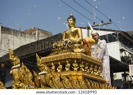 water flying around a golden Buddha statue during the songkran parade in Chiang Mai, Thailand - stock photo