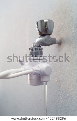 Water from filter tap with white wall.
