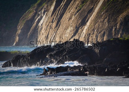 Waves splashing on volcanic rocks in the Galapagos Islands, Ecuador - stock photo
