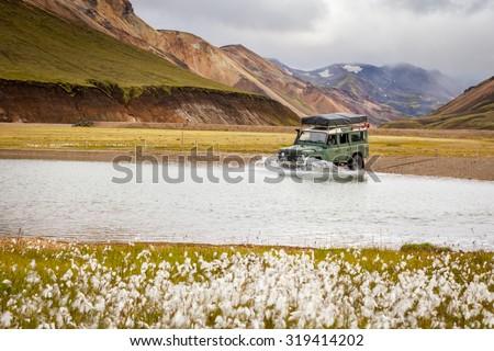 4WD car wades river in Landmannalaugar, Iceland - stock photo