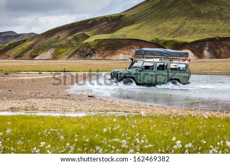 4WD car wades river in Landmannalaugar, South Iceland - stock photo