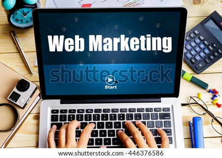 """Web marketing"" word on screen laptop with man hand work on it on wooden table with camera, spectacles, clock, pen and calculator - business, website, travel and blogging concept - stock photo"