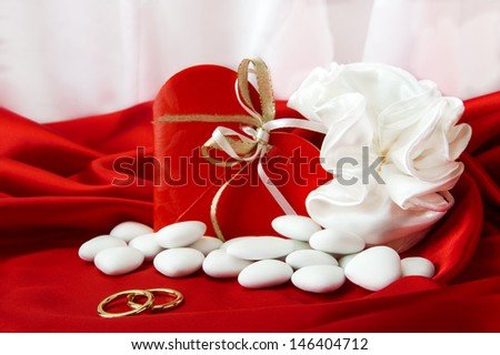 wedding rings and wedding favors on  elegant fabric background - stock photo