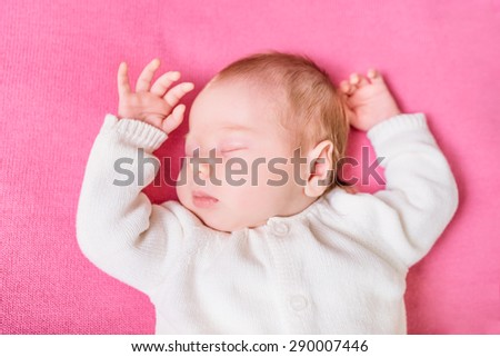 2 week old baby with closed eyes wearing knitted white clothes lying on pink plaid. Sweet little baby sleeping on pink sofa. Security and childcare concept. Selective focus on eye - stock photo