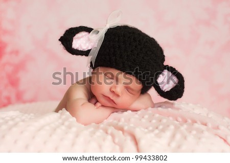 2 week old newborn girl wearing a black crocheted black sheep hat sleeping on a pink blanket with a pink background. - stock photo
