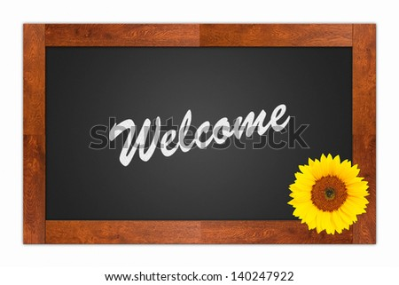 """Welcome"" written in chalk on a blank blackboard with sunflower on wooden frame, isolated on white background"