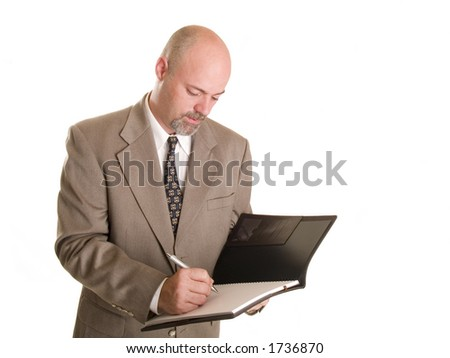 well dressed businessman taking notes in a notebook. - stock photo