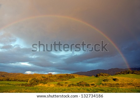 West Highlands Rainbow:  Fields at the Scottish West Highland, near Mallaig, on a cloudy sunset. As the sun found an opening in, it bathed the green fields with intense light. - stock photo