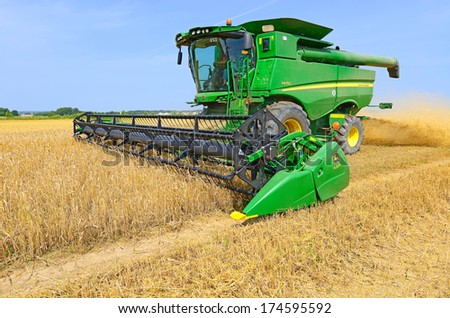 09/07/2013. Western Ukraine, near the town Kalush. Modern John Deere combine harvesting grain. - stock photo