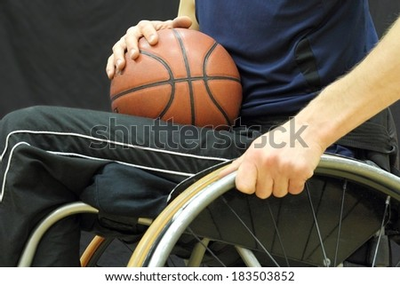 Wheelchair basketball player with ball on his lap - stock photo