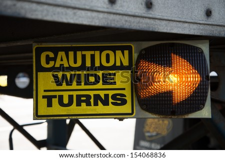18-Wheeler Caution Wide Turns Sign with Lighted Arrow.  Sign is on the undercarriage of a trailer on a big rig truck. - stock photo