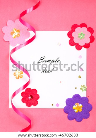 White blank card on pink paper background with flower (With sample text)