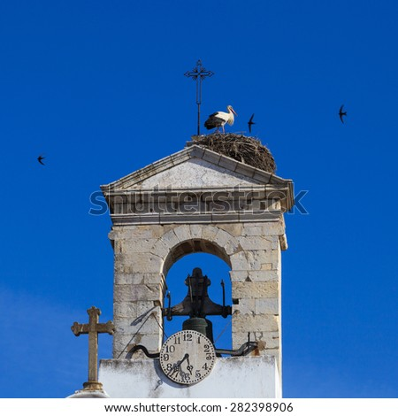 white cathedral tower. stork at the top of the church - stock photo