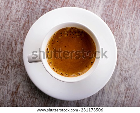white cup of coffee with foam on saucer, old wooden and painted  surface, top view  - stock photo