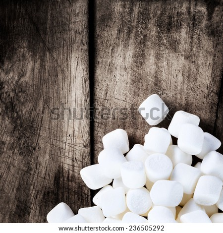 White Fluffy Round Marshmallows on wooden vintage  background with free blank copy space for text. Sweet  Food Candy Background as poster. wallpaper, backdrop  close up - stock photo