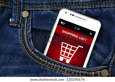 white mobile phone with  shopping cart in jeans pocket - stock photo