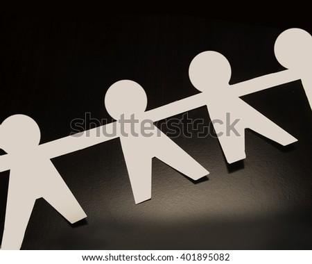 White paper people/Paper People/Human shapes cut out of paper on dark surface - stock photo