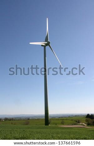 white wind turbine generating electricity on blue sky - stock photo
