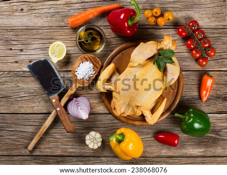 Whole raw chicken on a old wooden background with spices and vegetables , top view - stock photo