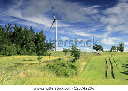 Wind turbine on the field crops - stock photo