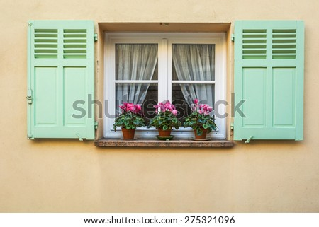 Window with Open Wooden Shutters, Decorated With Fresh Flowers - stock photo
