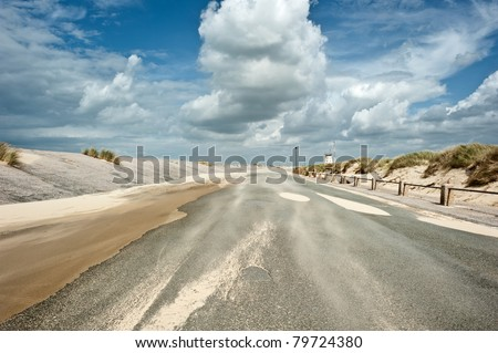 Windy coastal road on a sunny day with light clouds - stock photo
