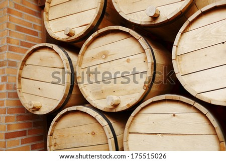 Wine barrels in a old wine cellar with wall bricks - stock photo