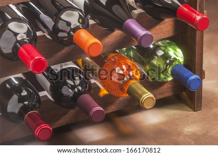 wine bottles stacked on wooden rack - stock photo
