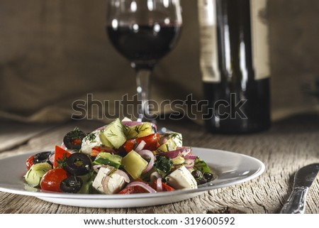 Wine. Greek. Salad in a small dish. Wooden table. Wine in a glass and a bottle of wine. Rustic style.