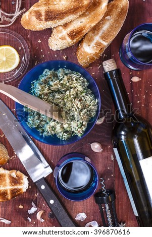 Wine, Italian cuisine, Wine in a blue glass on a wooden table and croutons or toast with arugula, avocado, parmesan, rustic style, top view,Closeup, top view, flat lay - stock photo