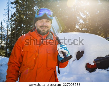 Winter, man is shoveling the car of snow - stock photo