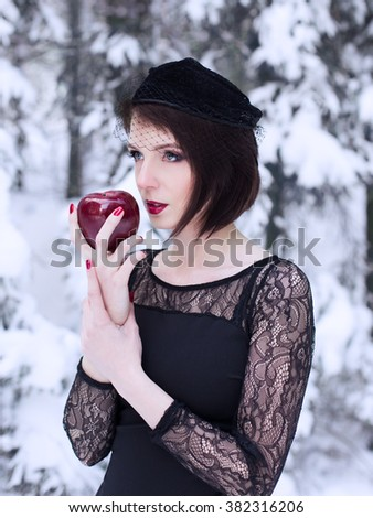 Winter portrait of the girl in the woods with a red apple