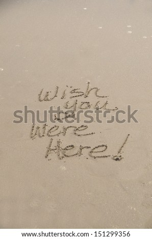 """""""Wish you were here,"""" a message written in the sand at the beach - stock photo"""