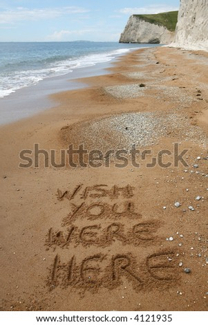 'Wish you were here' written in the sand on a peaceful beach - good copy area - stock photo