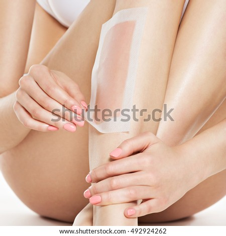 woman care her legs by waxing