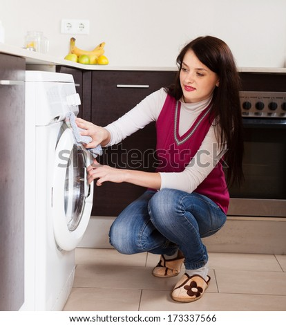 woman cleaning washing machine at home kitchen - stock photo