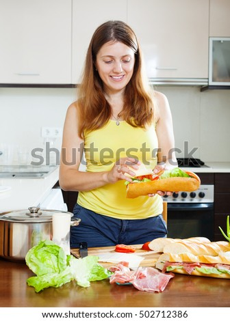 woman cooking sandwiches with cheese and  hamon