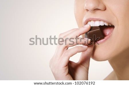 woman eating chocolate, close up - stock photo