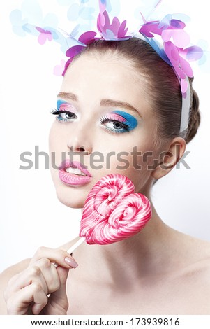 Woman eating lollipop Young woman with beautiful make-up eating lollipop