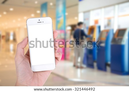 Woman hand showing smart phone with isolated screens display with Background of People Using ATM as Mobile Banking Concept - stock photo