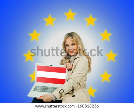 woman holding laptop with austrian flag on the screen and european union stars in the background - stock photo