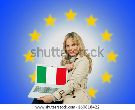woman holding laptop with italian flag on the screen and european union stars in the background - stock photo