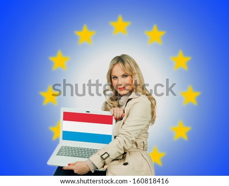 woman holding laptop with luxembourg flag on the screen and european union stars in the background - stock photo
