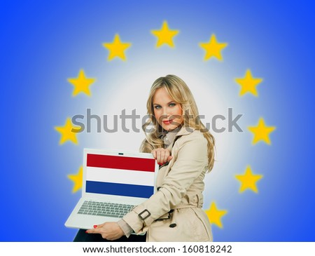 woman holding laptop with netherlands flag on the screen and european union stars in the background - stock photo