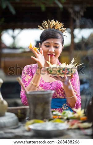 woman holding  offering for gods and praying in Bali temple  - stock photo