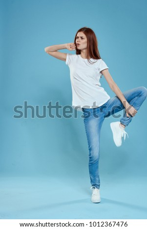 woman holds her leg on a blue background