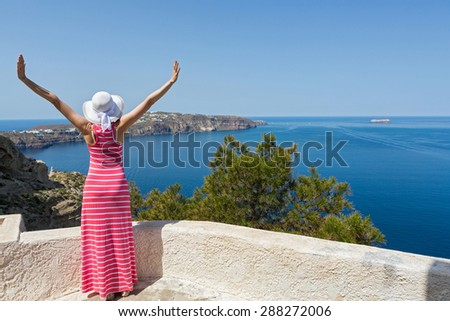 Woman in a long summer dress  watches the sea. Greece Santorini - stock photo