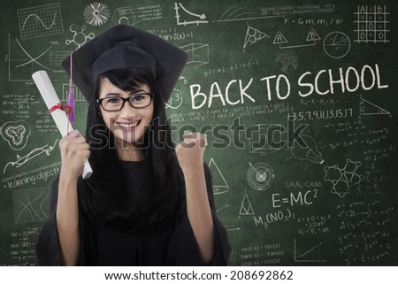 Woman in graduation gown expressing success in front of blackboard  - stock photo