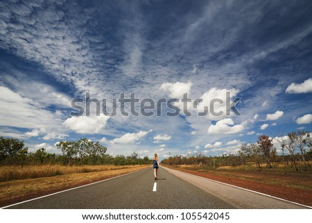 Woman is going through the road of outback vanishing in the desert, Outback Australia,  Northern Territory