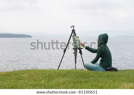 woman is painting. Open air session. - stock photo